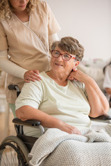 Positive old lady suffering form arthritis sitting at wheelchair in nursing home for elderly