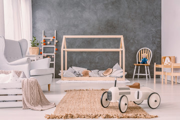 Car toy on rug near armchair in grey boy's room interior with wooden bed and chair. Real photo