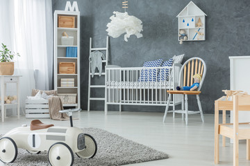 Chair next to bed under lamp in grey kid's bedroom interior with car toy on rug. Real photo