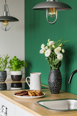 White roses in black and white vase next to coffee jug and big plate with cookies on wooden counter top