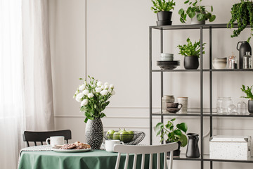 Industrial metal shelf with dishes and plants in bright dining room with round table with chairs