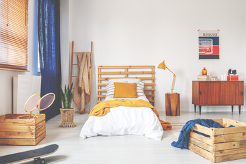 Real photo of a hipster bedroom interior with a bed, wooden boxes, badminton rackets and yellow pillow