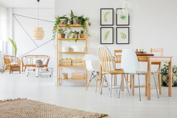 Natural linen rug on white wooden floor in trendsetting living and dining room interior with rattan sofa and armchairs and wooden table with modern chairs and gallery