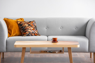 Wooden table with cup in front of grey sofa with pillows in simple living room interior. Real photo
