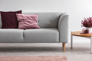 Heather on wooden table next to grey settee with cushions in bright living room interior. Real photo