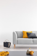 Yellow and black cushion on grey sofa in white loft interior with table and copy space. Real photo