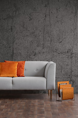 Orange pillows on grey couch in dark loft interior with concrete wall and wooden floor. Real photo