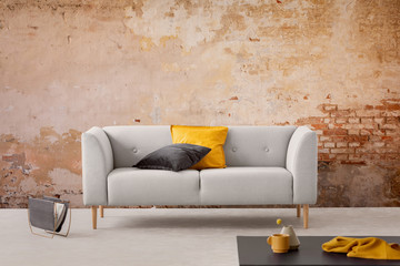 Black table and grey sofa with cushions in simple living room interior with red brick wall. Real photo