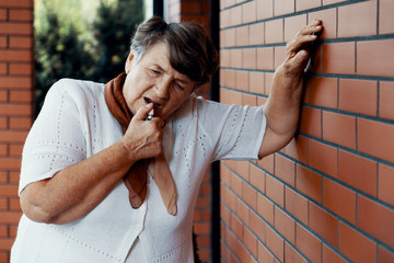 Breathless senior using inhaler and holding against a wall