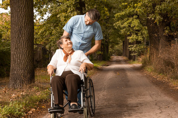 Male nurse taking for a stroll in park female senior in a wheelchair