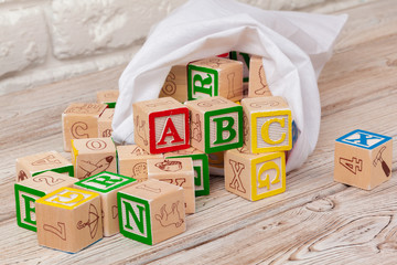 Multicolored wooden toy blocks on wooden background