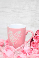 Pink porcelain coffee cup and pink heart roses