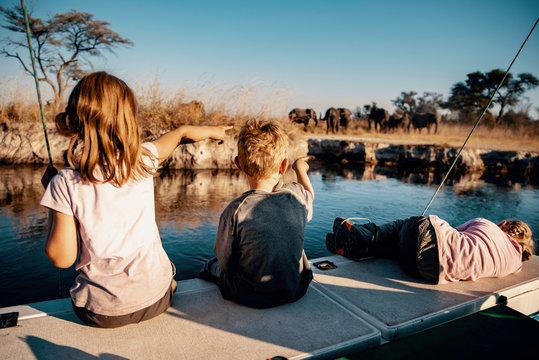Kinder beobachten Gruppe Elefanten am Ufer des Kwando River bei Sonnenuntergang, Caprivi, Namibia
