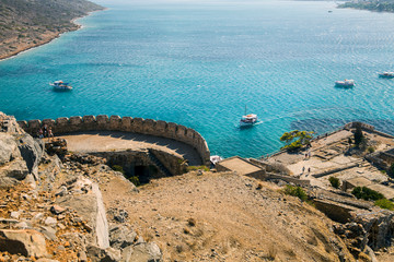 View from the Spinalonga fortress on the island. Boat trips to the island of lepers. Ships on the sea at the edge of the island.