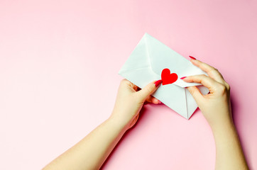 Female hand opens envelope with a red heart. A love letter to the beloved. Valentines day concept. Greeting valentine card. Declaration of love. Wedding invitation. View from above. Flat lay