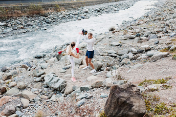 Beautiful young woman blonde in a tracksuit is practicing kickboxing with her teacher a man on nature against the background of a beautiful picturesque river. Concept sports lifestyle and strength