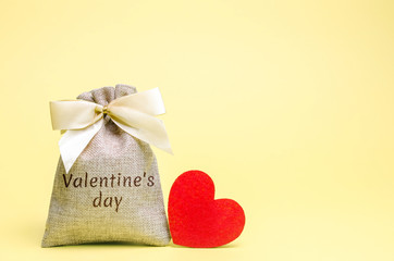 Bag with money and red heart with the word Valentine's Day. Saving money. Accumulation. Buying gifts to your loved one. Preparation for the holiday.