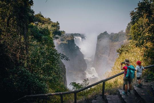 Touristin mit Kind fotografiert die Victoria Falls am späten Nachmittag mit Regenbogen, Sambesi, Simbabwe