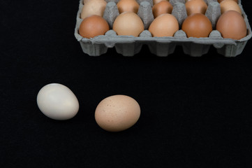 Two chicken eggs on black mat background with a carton box full of eggs