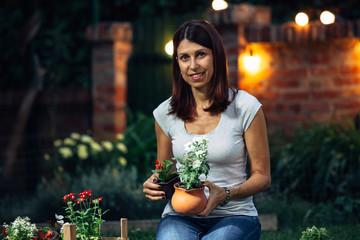 senior woman transplanting a seedling in her garden. night scene