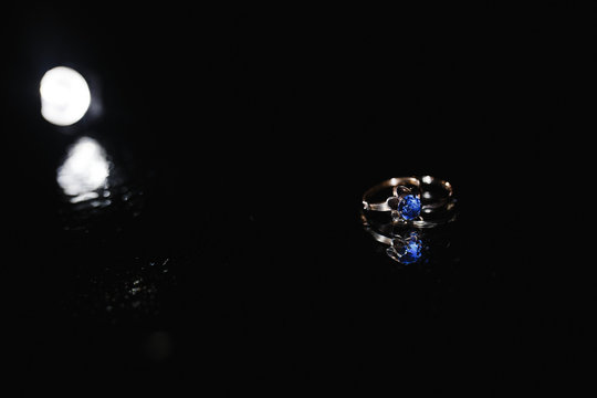 A ring with the blue diamond on the dark background.