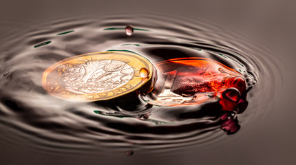 red water drop falling and splashing on a coin
