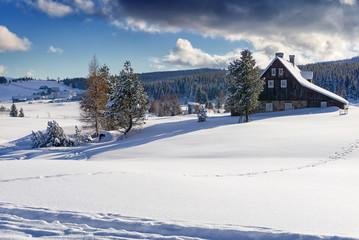 Winter mountain landscape in sunny day. Dark clouds on blue sky. Settlement Jizerka in Jizera Mountains in winter, Czech Republic.