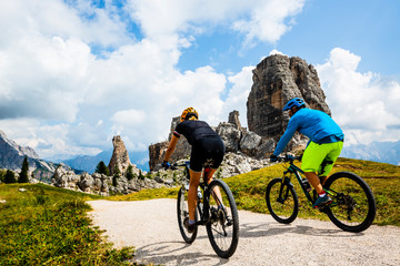 Foto auf AluDibond Radsport Couple cycling in Cortina d'Ampezzo, stunning Cinque Torri and Tofana in background. Woman and man riding MTB trail. South Tyrol province of Italy, Dolomites.