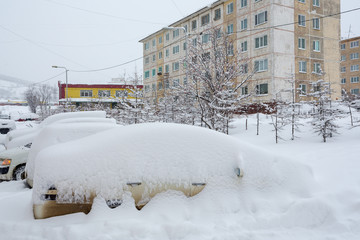 Cars covered with snow after a snowfall. Around the snowdrifts and a lot of snow on the machines. Snow on roofs, windshields and windows of cars. Cold winter weather. Magadan, Siberia, Far East Russia