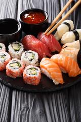 Japanese sushi food served on blackboard plate. Sushi roll with prawn, avocado, salmon, tuna, sesame close-up. Vertical