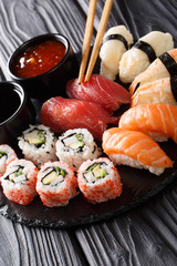 Japanese sushi food. Maki ands rolls with tuna, salmon, shrimp, crab and avocado with two sauces close-up on a slate. vertical