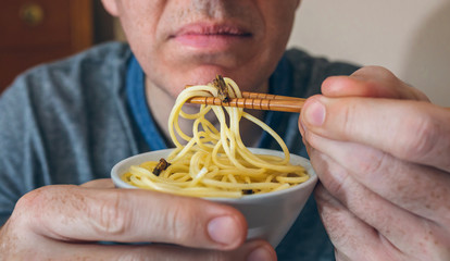 Unrecognizable man eating spaghetti and crickets with chopsticks