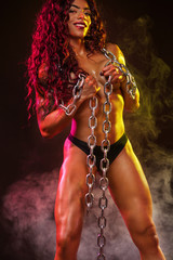 Topless fit woman dancer and athlete with chains posing on black background with colorful lights.