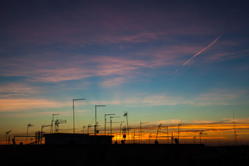 Sunrise in the city with silhouette of antennas