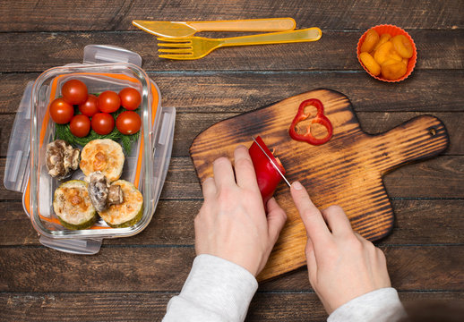 Woman preparing takeaway meal for children. School lunch box with salad, stuffed vegetable marrow, baked mushrooms and dried apricots. Healthy eating habits concept.