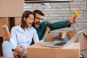 Young happy couple buying over the Internet in a new home