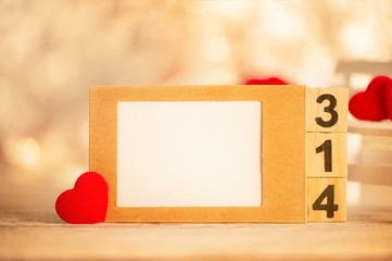 Concept of Valentine, anniversary, wedding greeting with a picture frame, heart shapes on a white wooden bench, bokeh background, close up