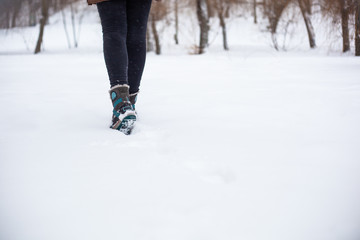 The girl walks in the snow in dark jeans and gray boots with blue soles and blue stripes