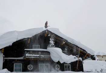 A man shovel snow on a rooftop after heavy snowfall in the village of Ramsau
