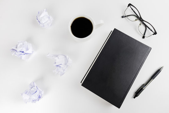 Tabletop of a writer/ content creator. Flat lay with crumpled paper, coffee cup, glasses, book and pen on a white table.