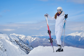 Portrait of beautiful woman with ski and ski suit in winter mountain. Wall mural
