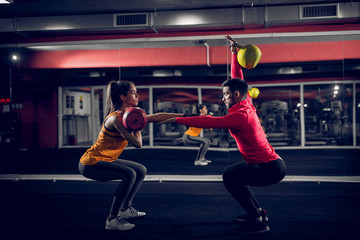 Couple goals. Fit young couple working out in a gym . Doing squats while holding weights in their hands.