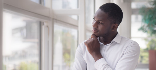Thoughtful African man thinking; portrait of pensive young adult african man thinking or planning; good idea, future, brain storming concept; African young adult black man model