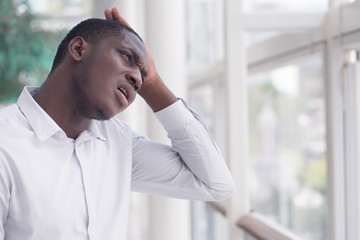 Unhappy, failed African man shrugging with problem; portrait of upset African black man feeling frustrated with problem, bad issue, failure, unhappiness; African young adult man model
