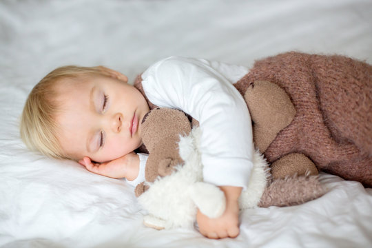 Sweet baby boy in cute overall, sleeping in bed with teddy bear stuffed toys, winter time