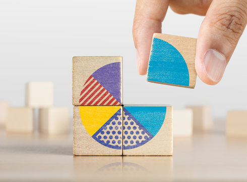 Market share, business opportunity, market growth, increase market share or business concept. Businessman grabs a piece of wooden blocks with pie chart graphic.