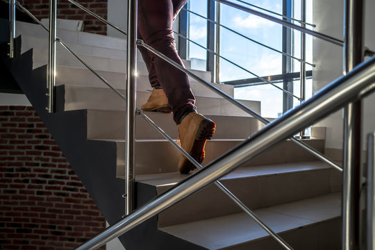 bottom view of a young man hurry and running up the stairs with metal railings