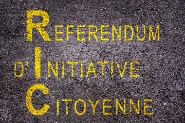Word RIC (meaning referendum at citizen's initiative) on asphalt background