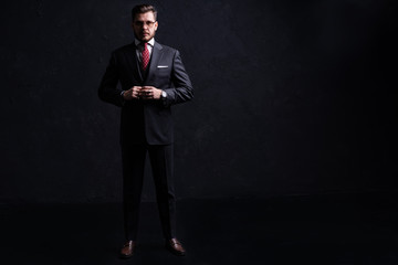 Full length portrait of a fashion male model over black background. Looking at camera.