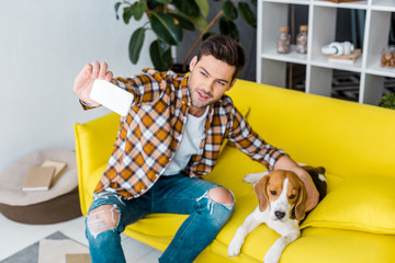 happy man taking selfie on smartphone with cute dog
